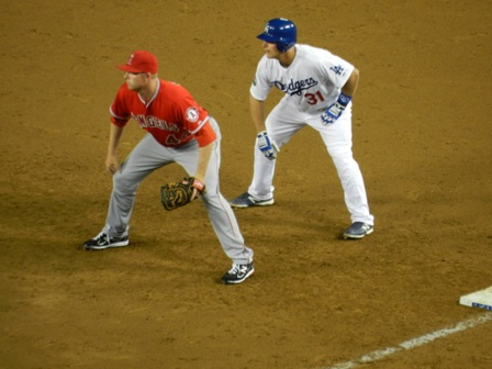 From 2012's Spring Training Freeway Series games: Angels jack of many trades and chief bomb hitter, Mark Trumbo, and Dodgers catcher Tim Federowicz move with the pitch. Angels at Dodgers, April 3, 2012. Photo by This is a very simple game...