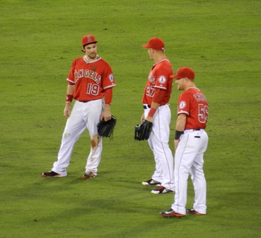Collin Cowgill, Mike Trout and Kole Calhoun kick back in the outfield during a pitching change. Whatever tale Collin's spinning, Kole is clearly having none of it, but Mike might believe him...might. Angels vs. A's, September 23, 2013. Photo by This is a very simple game...